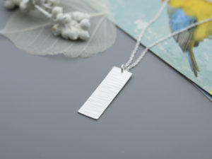 Rectangular sterling silver pendat with cross pein pendant