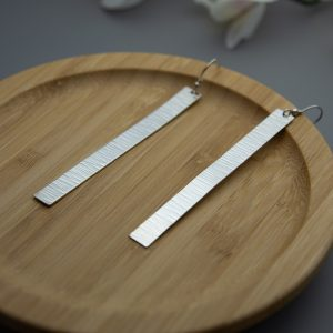 Long thin handmade sterling silver earrings with a cross pein textured effect