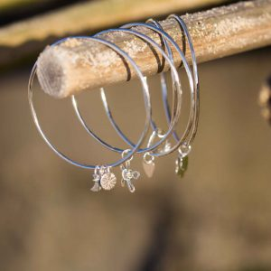 A mix of sterling silver bangles with a sun, moon and star attahed