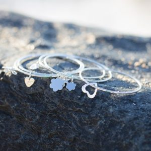 A mix of sterling silver bangles with a tiny heart attached